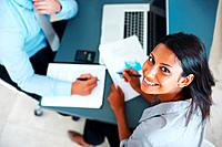Top view of smiling young businesswoman working with her colleague on business development _ Discussion