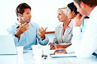 Confident young businessman sitting with his associates guiding on business project