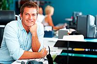 Happy young businessman sitting at desk with colleagues working in background