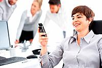 Beautiful business woman reading text message on cell phone with team discussing in background