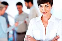 Portrait of confident business woman with colleagues discussing in background