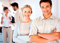 Confident business man and woman smiling with colleagues discussing in background