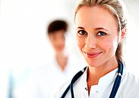 Closeup of female doctor giving you cute smile with colleague in background