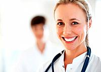 Closeup of beautiful female doctor smiling with colleague in background