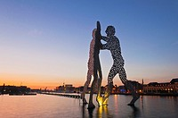 Molecule Man, sculpture by American artist Jonathan Borofsky, staging in the Spree river at sunset, overlooking the Oberbaumbruecke bridge, Friedrichs...