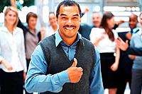 View of businessman giving thumbs up with exuberant team in background