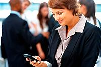 Young female executive texting on mobile phone