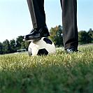 Businessman´s Foot Resting on Soccer Ball