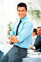 Business man smiling with hands folded during meeting