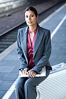 Businesswoman with Suitcase on Railroad Platform