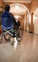 Woman in Wheelchair in Corridor