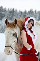 young woman in a revealing Santa costume leaning against a white horse in a winter landscape