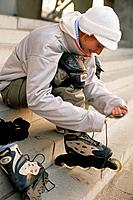 Young Woman in Hat Tying Laces on Inline Skates