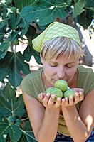 Woman Smelling Figs in Her Hands in Front of Fig Tree