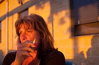 Woman relaxing in the evening sunlight with a cigarette