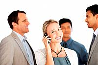 Cheerful business woman using cellphone with colleagues discussing in background