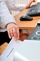 Hand reaching resignation letter from printer