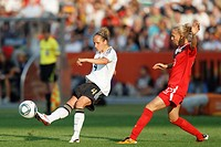BERLIN, GERMANY - JUNE 26: Babett Peter L of Germany passes the ball ahead of Brittany Timko R of Canada during the opening match of the FIFA Women´s ...