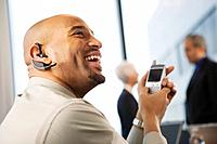 Businessman Using Cell Phone and Earphone