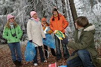 teenagers collecting garbage in a winter forest