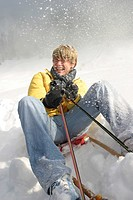 teenage boy sitting on a toboggan laughing while being pelted with snow