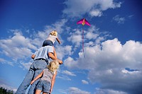 Father and two daughters flying a kite