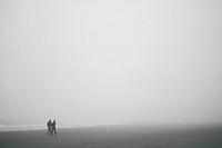 Couple walking in the Fog, Chesterman Beach, Tofino, British Columbia.