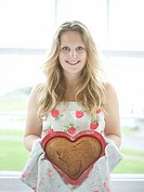 Teenage girl holding heart shaped cake