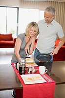 Man serving breakfast to wife