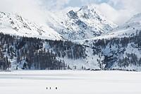 Walk over frozen Silser lake, Isola village in the background, Grisons, Switzerland