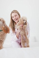 Woman playing with dog on bed