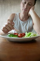 Man Sitting in Front of Plate with Salad