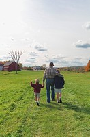 Father walking with his two sons over meadow