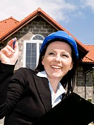 engineer woman in helmet with house in background