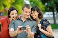 Man photographing himself with two female friends using cell phone