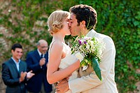 Newlyweds kissing at marriage ceremony