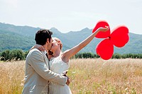 Newlyweds kissing in field with red heart shape balloons