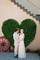 Newlyweds by heart shaped bush