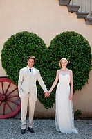 Newlyweds by heart shaped bush holding hands (thumbnail)