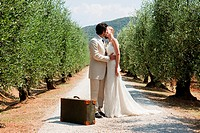 Newlyweds kissing on country road with suitcase (thumbnail)