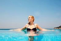 Young woman in infinity pool, looking away (thumbnail)