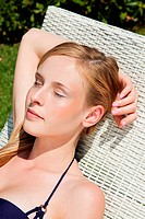 Young woman sleeping on sun lounger, close up