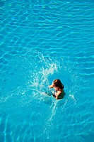 Young woman jumping into swimming pool