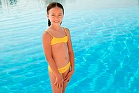 Girl in yellow bikini by swimming pool, portrait