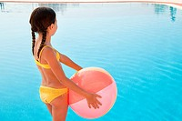 Girl with beach ball by swimming pool