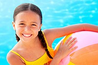 Girl with beach ball by swimming pool, portrait