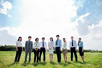 Businesspeople in a row in field (thumbnail)