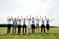 Businesspeople in a row in field, arms up