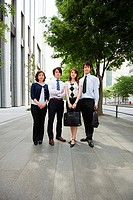 Four businesspeople on sidewalk