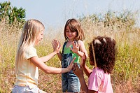 Girls playing pat a cake in field